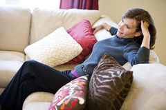 Mature woman relaxing on living room sofa Royalty Free Stock Photography