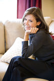 Mature woman relaxing on living room sofa Royalty Free Stock Photos