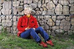Mature woman relaxing outdoors. Mature woman relaxing on grass outdoors with stone wall in background Stock Photo