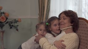 Mature woman sitting in a rocking chair and her small cute granddaughters came to her to kiss and gently hug. Mature woman relaxing in a rocking chair with cup stock video