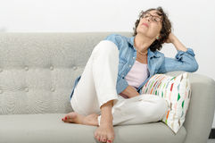 Mature woman relaxing on a sofa Stock Photography