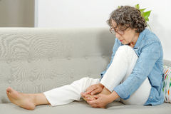 Mature woman relaxing on a sofa Royalty Free Stock Images