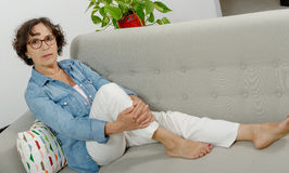 Mature woman relaxing on a sofa Stock Photo