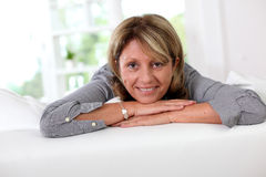 Mature woman relaxing on sofa Stock Images