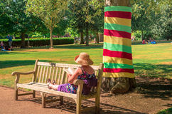 Mature woman relaxing in a sunny day in a park of UK. The woman, with straw hat and reading a book, is seen at her back with her legs stretched on a bench by a royalty free stock photography