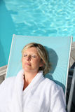 Mature woman relaxing by the swimming pool Royalty Free Stock Photography