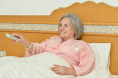 Mature woman with remote control Stock Photo