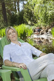 Mature woman resting in chair with man and son fishing in the background Royalty Free Stock Images