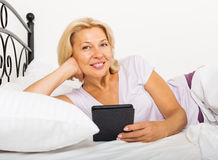 Mature woman resting with ereader Royalty Free Stock Images