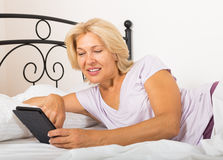 Mature woman resting with ereader Stock Images