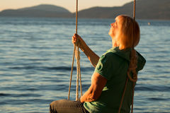 Mature woman resting on swing at beach 2 Royalty Free Stock Image
