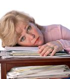 Mature woman rests head on papers Royalty Free Stock Image