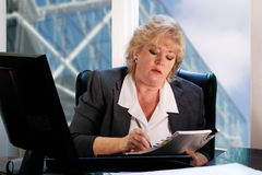 Mature woman reviewing papers Royalty Free Stock Image