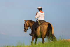 Mature woman riding an Andalusian horse Royalty Free Stock Image