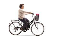 Mature woman riding a bicycle royalty free stock photos