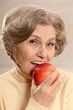 Mature woman with ripe apple Royalty Free Stock Images