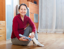 Mature  woman rubbing wooden floor with rag and cleanser. At home Royalty Free Stock Photography