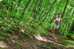 Mature Woman Runner. Mature woman running in forest stock photo