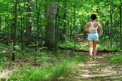Mature Woman Runner. Mature woman running in forest royalty free stock photography