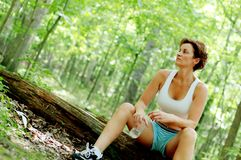 Mature Woman Runner Resting. In woods stock photo