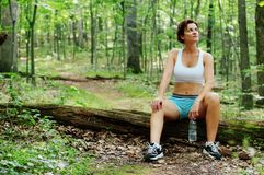 Mature Woman Runner Resting. In woods royalty free stock photography