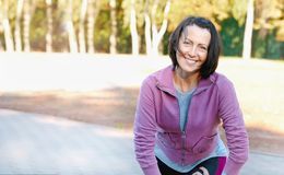 Mature woman runner taking a rest after running in the park. Healthy lifestyle concept royalty free stock image