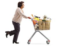 Mature woman running and pushing a shopping cart filled with gro. Full length profile shot of a mature woman running and pushing a shopping cart filled with stock photography