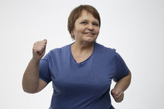 Mature woman running in a studio with a gray background. Mature woman running with hands Royalty Free Stock Images