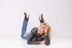 Mature woman 40s lying on floor, looking sideways. White background royalty free stock image