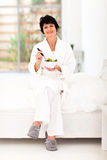 Mature woman salad. Pretty mature woman holding bowl of salad sitting on bed Royalty Free Stock Photos
