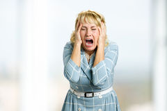 Mature woman screaming in despair. Royalty Free Stock Image