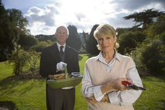 Mature woman with secateurs by butler with basket of gardening tools, portrait Royalty Free Stock Photography