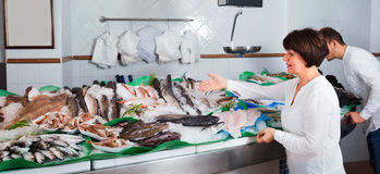 Mature woman selecting cooled fish at fishery Royalty Free Stock Images