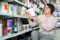 Mature woman selecting hair care products. In shop and smiling stock photo