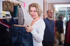 Mature woman selecting jeans in the shop. Beautiful mature women selecting jeans in shopping center Stock Photos