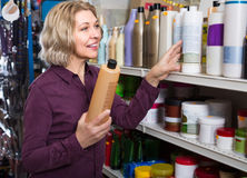 Mature woman selecting shampoo in store. Smiling aged woman selecting  shampoo in beauty store Stock Photo