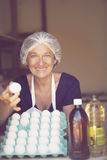 Mature woman selling eggs Stock Image