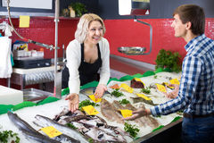 Mature woman selling fish to male Royalty Free Stock Photography