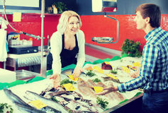 Mature woman selling fish to male. Portrait of mature women selling fish to male customer in store Stock Image