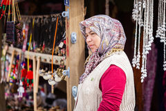 Mature Woman Selling Trinkets in Assos Turkey. ASSOS, TURKEY – APRIL 23: Unidenified woman in head scarf selling trinkets and souvenirs during buildup to Anzac Royalty Free Stock Photo