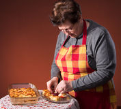 Mature woman serving apple pie Royalty Free Stock Photos
