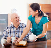 Mature woman serving breakfast to husband Stock Photo