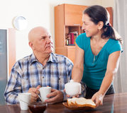 Mature woman serving tea for her  man Royalty Free Stock Photos