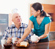 Mature woman serving toast to  happy husband Royalty Free Stock Images