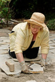 Mature woman setting pavers Stock Photo