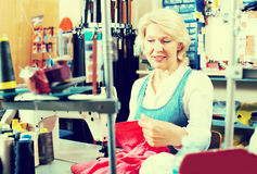Mature woman sewing with professional machine Stock Images