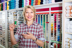 Mature woman in sewing store Royalty Free Stock Photo