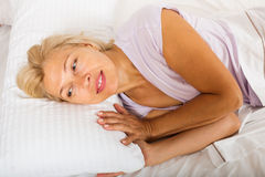 Mature woman in shirt laying on bed at bedroom Stock Photos