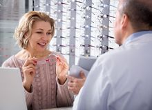 Mature woman shopper consults with professional male optics on the selection of spectacles. Charming mature women shopper consults with professional male optics Stock Photo