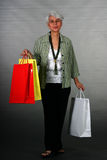Mature woman shopping. Attractive mature woman showing off her shopping bags Royalty Free Stock Images
